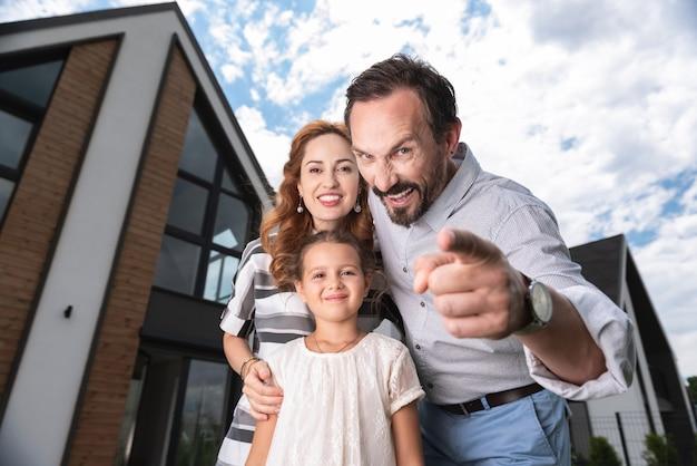 Homem alegre e simpático apontando para você enquanto está junto com sua família