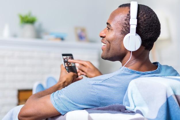 Homem alegre e simpático, sentado no sofá e segurando o smartphone enquanto desfruta da música