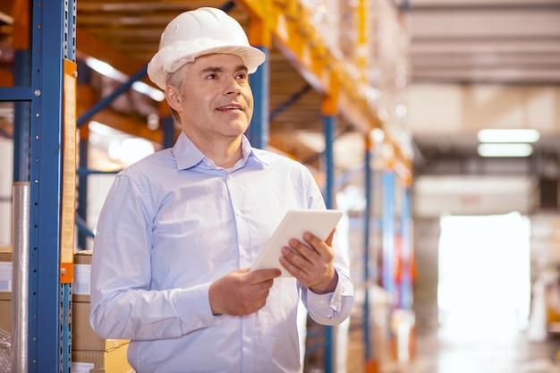 Homem alegre e simpático trabalhando como gerente de logística no armazém