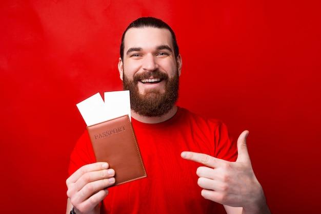 Homem alegre e sorridente com barba apontando para passaporte e ingressos na parede vermelha