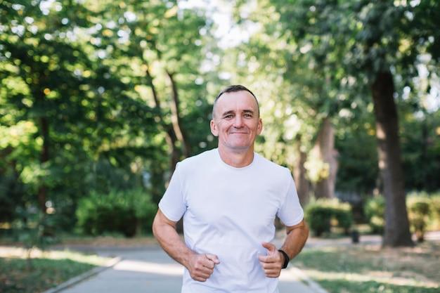 Homem alegre em camiseta branca correndo em um parque