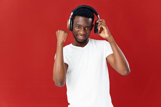 Homem alegre em fones de ouvido em uma camiseta branca ouvindo música, entretenimento de fundo vermelho