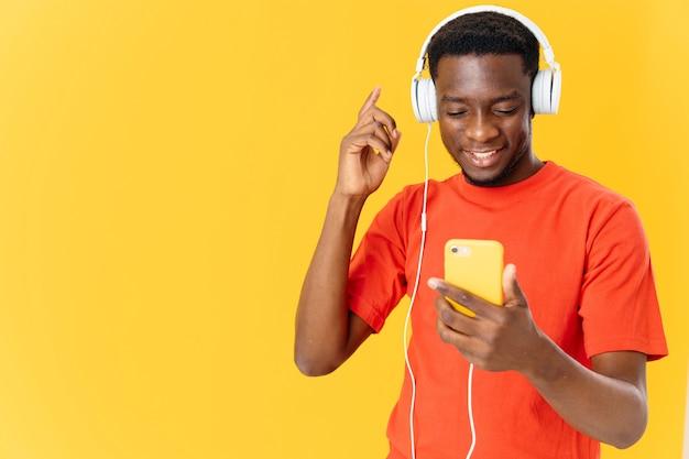Homem alegre em fones de ouvido, ouvindo música, estilo de vida, fundo amarelo