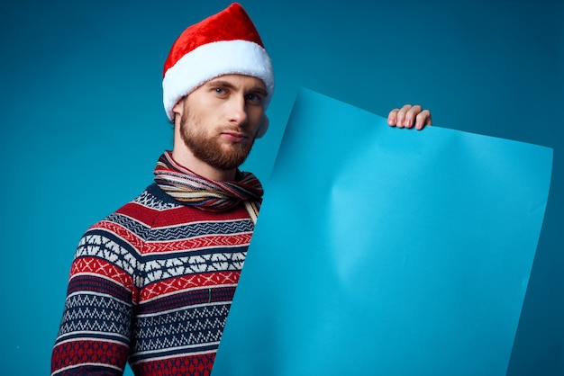 Homem alegre em um pôster de maquete azul de natal com fundo isolado