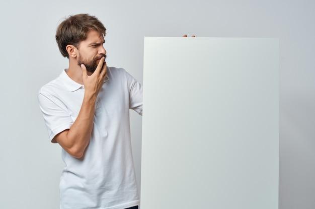 Homem alegre em uma camiseta branca pôster mocap com desconto anunciando estúdio copyspace