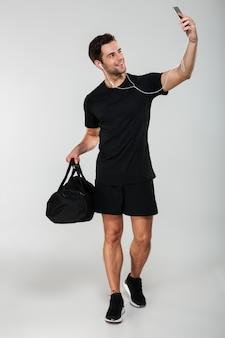 Homem alegre esportes fazer selfie com saco por telefone celular