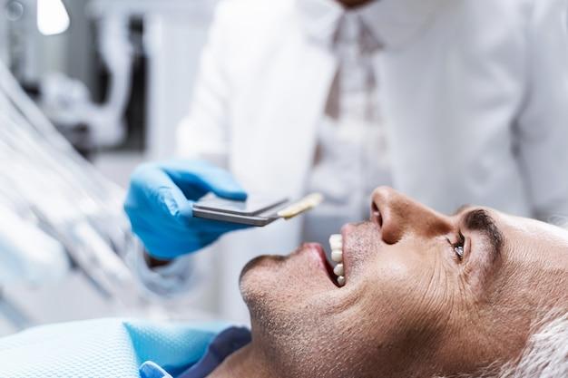 Homem alegre está deitado na cadeira do dentista enquanto o dentista o prepara para procedimentos dentais