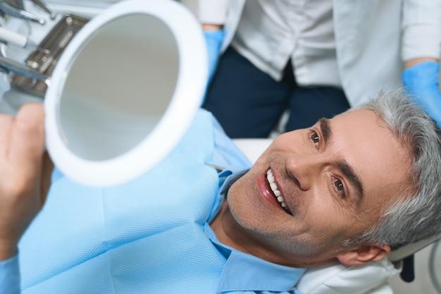 Homem alegre está deitado na cadeira e olhando no espelho enquanto se delicia com o trabalho do dentista