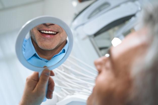 Homem alegre está olhando no espelho e apreciando o reflexo de seu sorriso após procedimentos odontológicos.