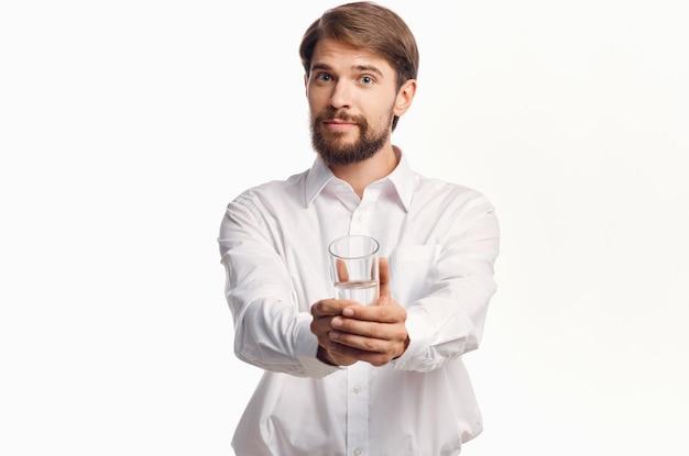 Homem alegre estende a mão com um copo d'água para a frente em uma luz.