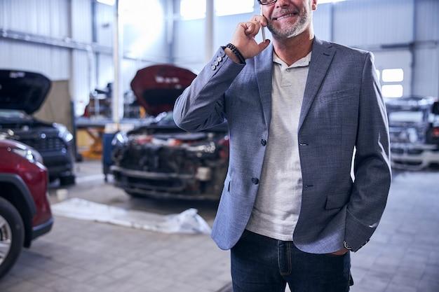 Homem alegre falando ao celular em uma oficina mecânica