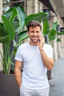 Homem alegre falando ao telefone