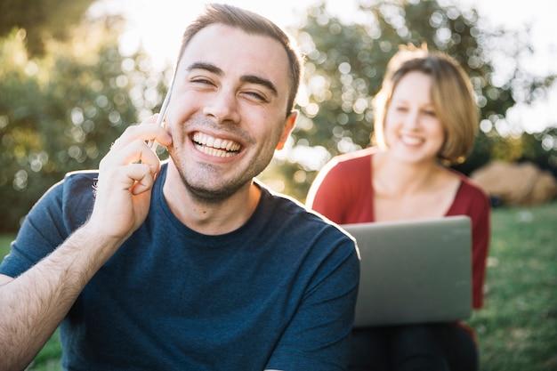 Homem alegre, falando no telefone perto de mulher turva com laptop