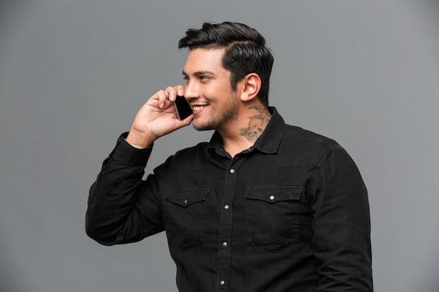 Homem alegre falando por telefone.