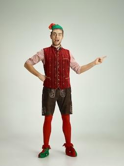 Homem alegre fantasiado de elfo apontando algo com o dedo