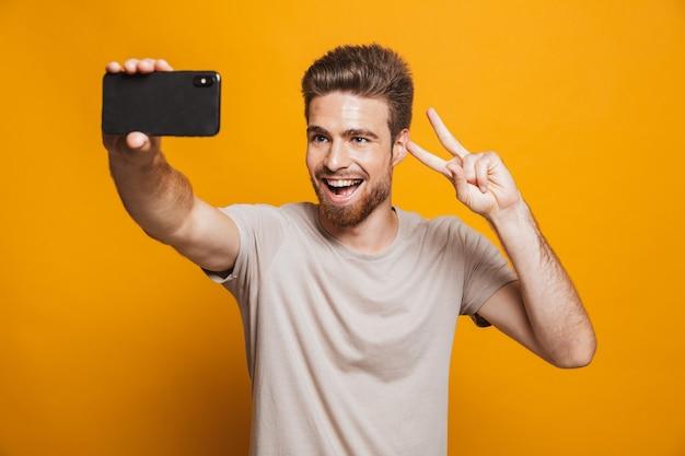 Homem alegre faz uma selfie por smartphone com gesto de paz.