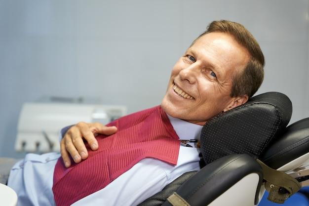 Homem alegre fazendo exame dentário na clínica