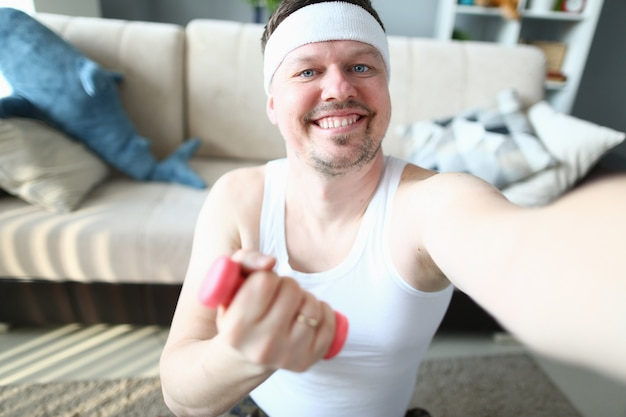 Homem alegre fazendo selfie durante treino matinal em casa