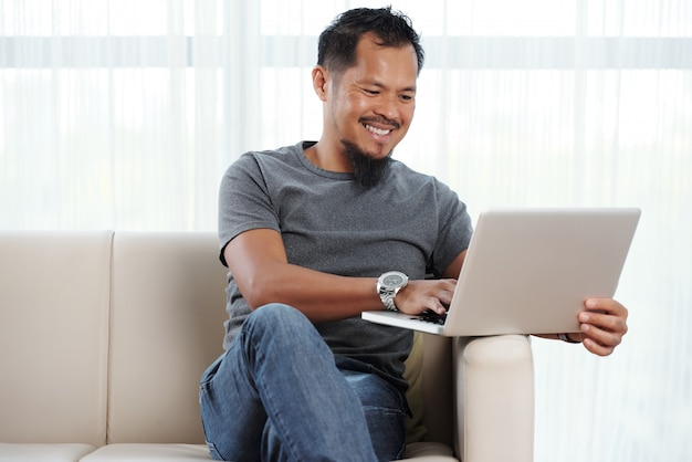 Homem alegre filipino com laptop