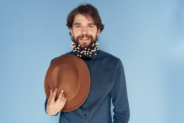 Homem alegre floresce com chapéu de barba na mão.