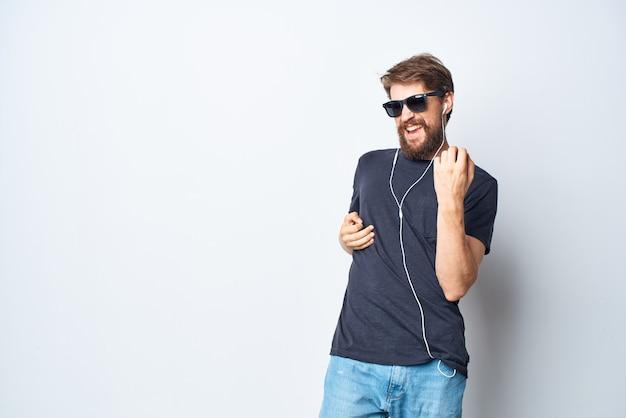 Homem alegre, fones de ouvido, óculos de sol, música, dança, diversão, estúdio, estilo de vida