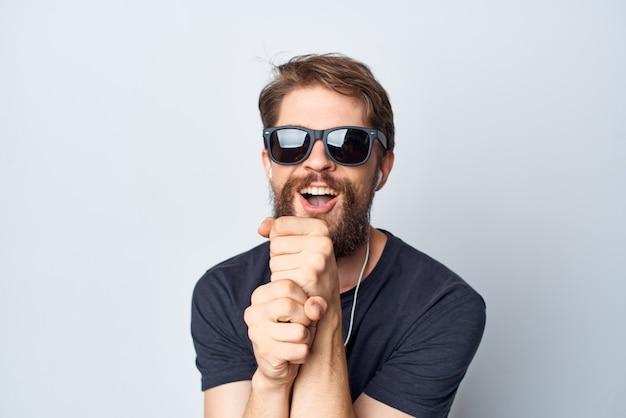 Homem alegre, fones de ouvido, óculos de sol, música, dança, diversão, isolado, fundo