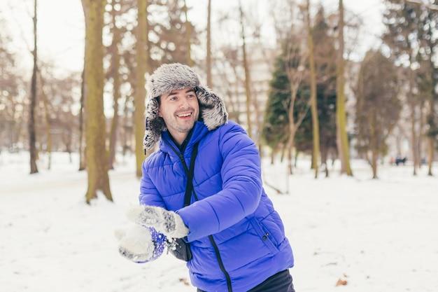 Homem alegre gosta da neve no parque, joga neve no inverno