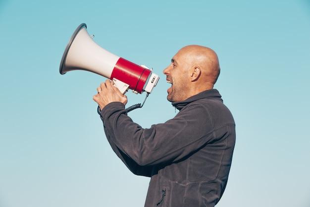 Homem alegre gritando, gritando através de um megafone, anunciando algo novo, conceito de anúncios