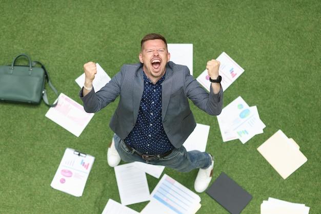 Homem alegre levanta as mãos e grita no chão mentindo sobre gráficos de negócios