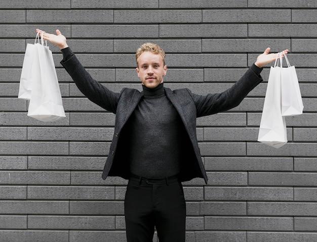 Homem alegre, levantando as sacolas de compras