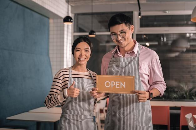 Homem alegre. marido bonito de cabelos escuros usando óculos e se sentindo feliz abrindo restaurante com a esposa