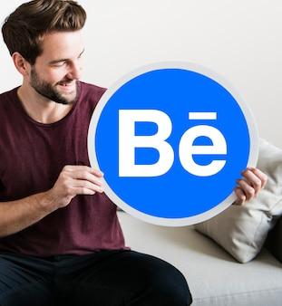 Homem alegre, mostrando um ícone do behance