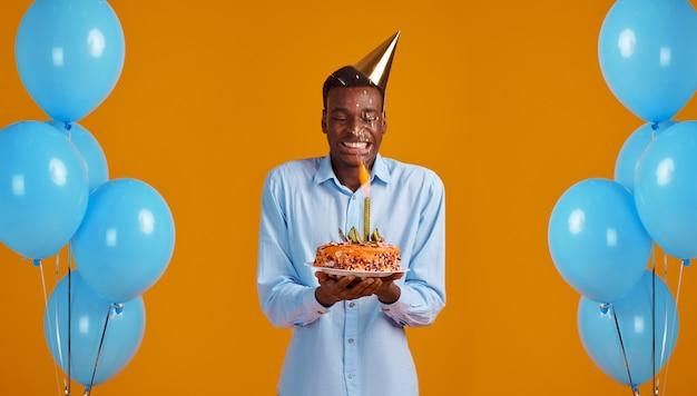 Homem alegre na tampa segurando o bolo de aniversário com fundo amarelo, fogos de artifício. homem sorridente tem surpresa, comemoração do evento, decoração de balões