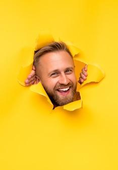 Homem alegre olhando através de um papel rasgado