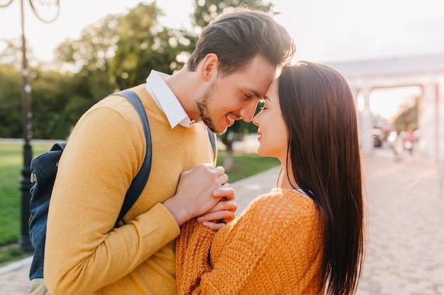 Homem alegre olhando para uma mulher de cabelos escuros com ternura num bom dia de outono