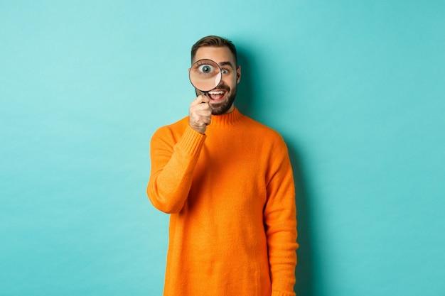 Homem alegre procurando por algo, olhando pela lupa e sorrindo feliz, encostado na parede turquesa