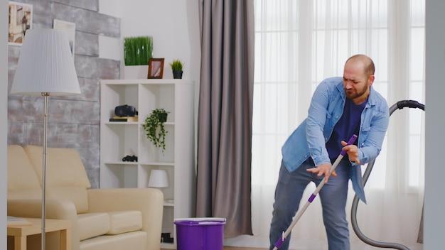 Homem alegre se divertindo enquanto limpa a casa com um esfregão moderno