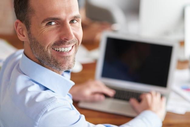 Homem alegre se virando e sorrindo enquanto trabalha no computador
