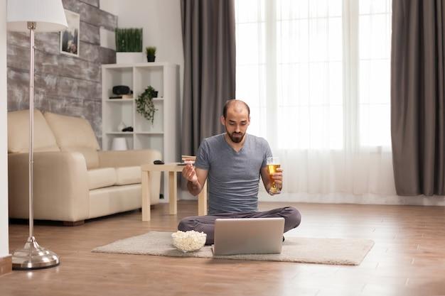 Homem alegre, segurando cerveja e comendo pipoca durante uma videochamada com amigos.