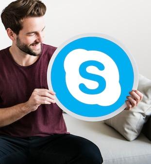 Homem alegre, segurando um ícone do skype