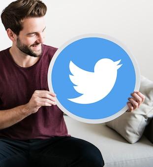 Homem alegre, segurando um ícone do twitter
