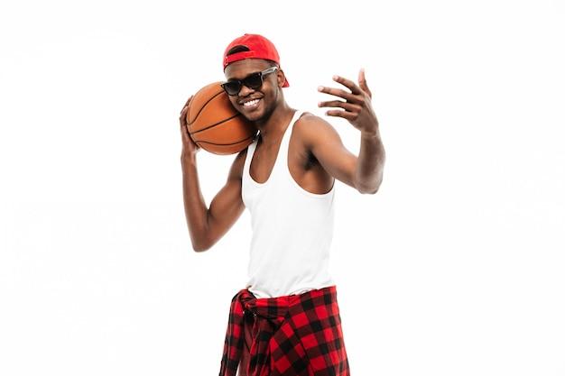 Homem alegre, segurando uma bola de basquete e convidando para jogar