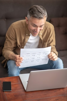 Homem alegre segurando uma folha com texto perto do caderno