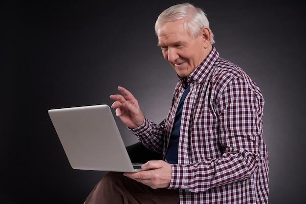 Homem alegre sentado com laptop