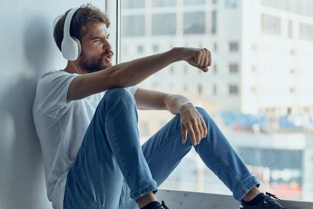 Homem alegre sentado no parapeito da janela, estilo de vida