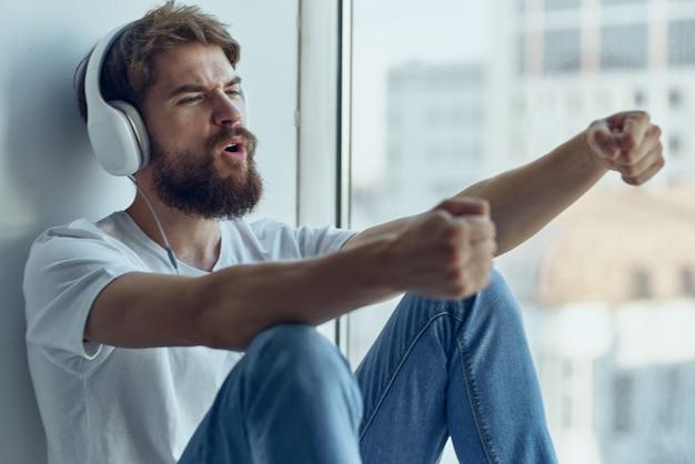 Homem alegre sentado no parapeito da janela relaxando