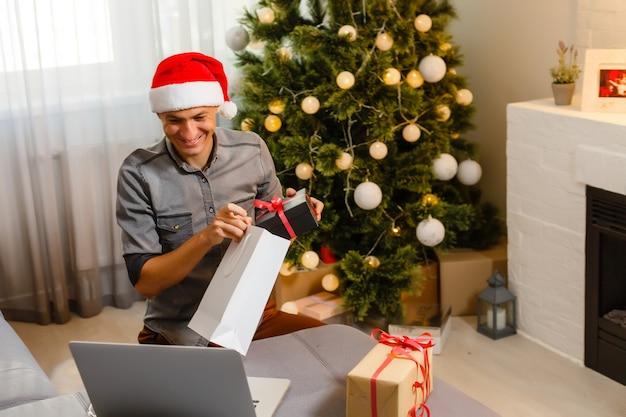 Homem alegre sentado no sofá usando laptop perto da árvore de natal em casa