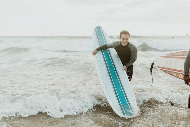Homem alegre surfando na praia