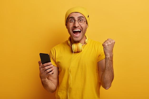 Homem alegre torce e comemora a vitória no jogo para smartphone, levanta o punho, se alegra ao terminar o nível difícil, usa roupas elegantes e vivas