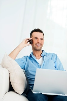 Homem alegre usando laptop e falando no celular